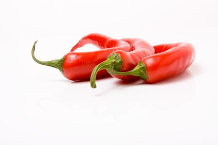 Three vibrant red chillis on a backdrop of dark slate. photo