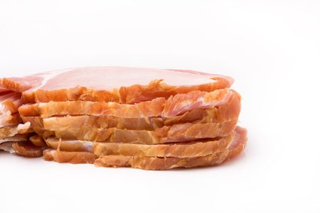 uncooked bacon: Pile of raw uncooked Sliced bacon isolated against white background from low viewpoint.