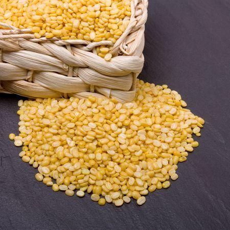 Vibrant yellow Moong Daal lentils or mung bean lentils against dark slate. photo