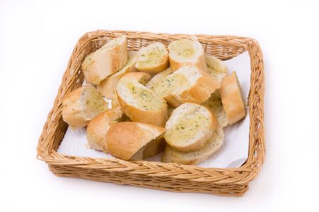 browned: Garlic bread in wicker basket isolated against white background. Stock Photo