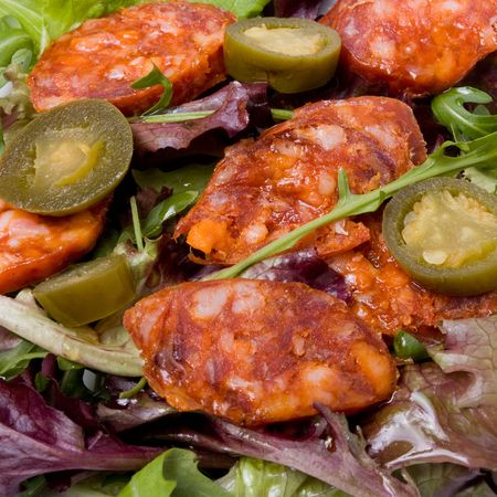 Spicy Mediteranian Salad of chorizo sausage with jalapeno chillis and herby salad leafs. photo