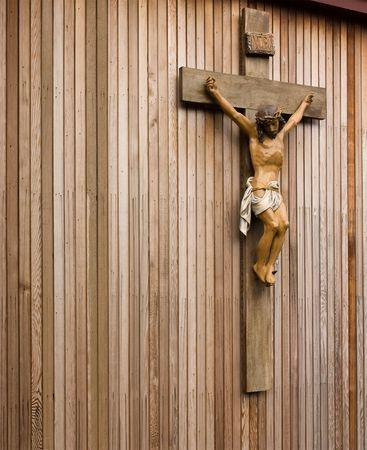 Statue figure of Jesus crucified on wooden cross against wooden panneled wall. Stock Photo - 6606080