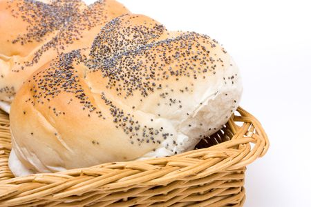 Seeded bread roll in wicker basket from low viewpoint isolated against white background. photo