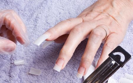arthritic: Older senior womans hand recieving home spabeauty treatment of nail extensions.