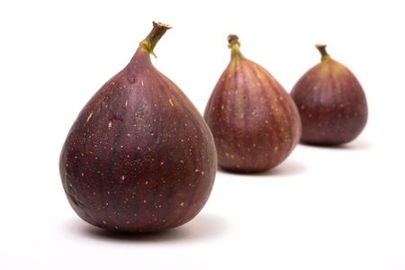 halved  half: Abstract arrangement of Three ripe figs isolated against white background. Stock Photo