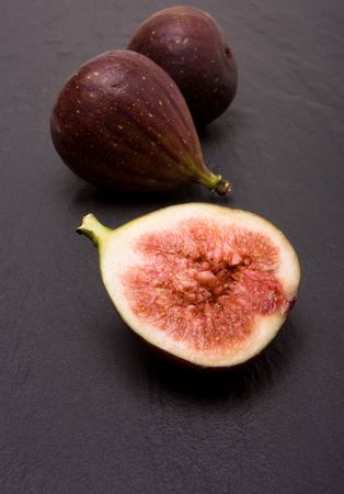 dark grey slate: Figs one halved against background of dark grey slate.
