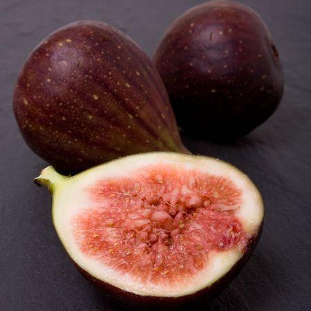 dark grey slate: Close up of Figs one halved against background of dark grey slate.