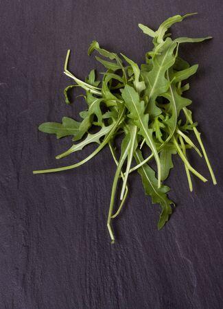 Pile of rocket leaf salad against dark slate background. photo