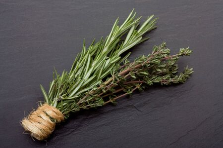 Bunches of Rosemary and Thyme bound with string against dark slate background. Stock Photo