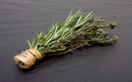 Bunches of Rosemary and Thyme bound with string against dark slate background. photo