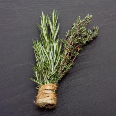 dark slate gray: Bunches of Rosemary and Thyme bound with string against dark slate background.