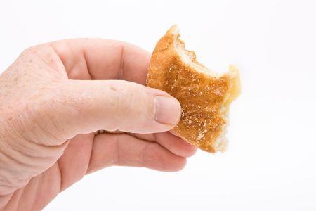 Hand holding half eaten donut against white background. Stock Photo - 6828145
