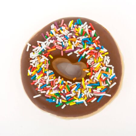 Chocolate Doughnut with vibrant multicoloured sprinkles isolated against white. Stock Photo