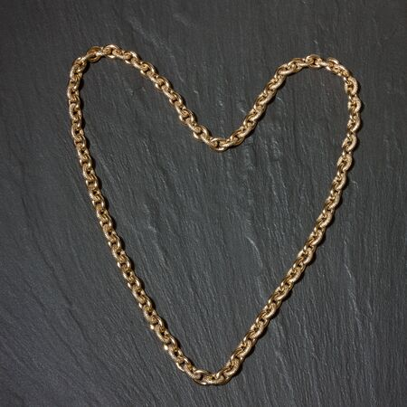 costume jewelry: Heart shape chunky gold chain on background of dark slate to depict the concept of wealth. Stock Photo