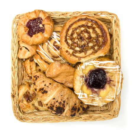 Overhaead view of Wicker basket with selection of French & Danish pastries on white background. photo