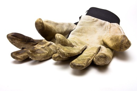 grubby: Pair of grubby gardening gloves from low perspective isolated against white background.