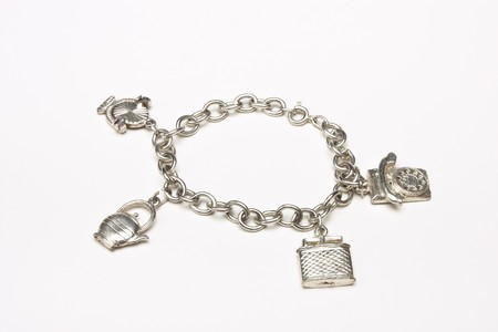 a bracelet: Small silver charm bracelet with 4 charms isolated against white background. Stock Photo