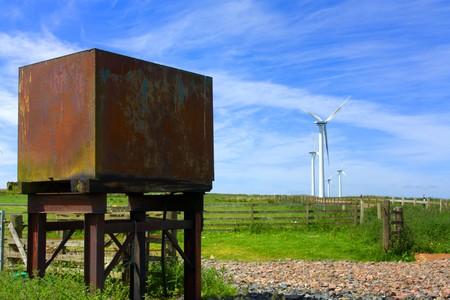eyesore: Old Rusty water tank next to Wind farm set in the rolling hills of Fala Moor, Midlothian, Scotland.