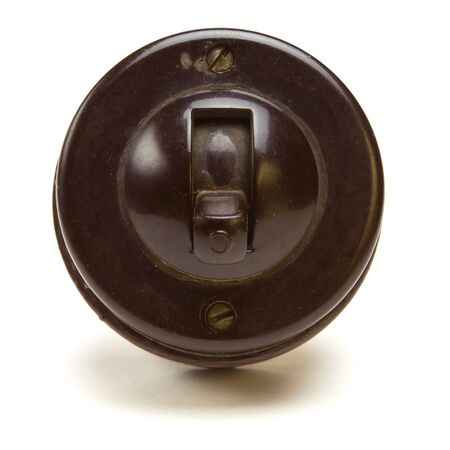 bakelite: Old Vintage bakelite light switch isolated against white background from low perspective.