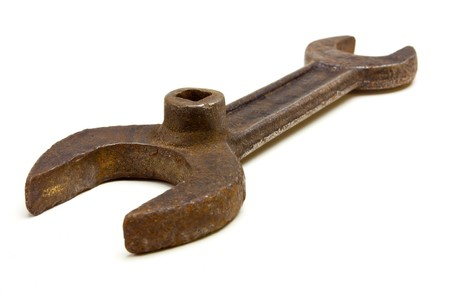 Old rusty welding gas bottle key spanner from low viewpoint isolated against white. photo