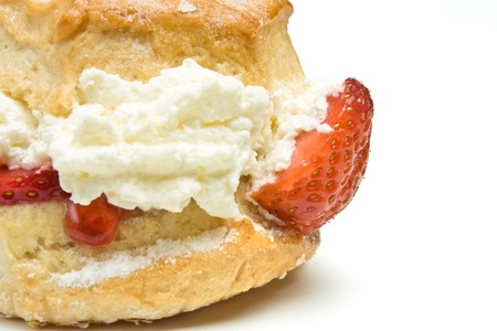 whitebackground: Cream Scone with strawberry from low perspective isolated against whitebackground.