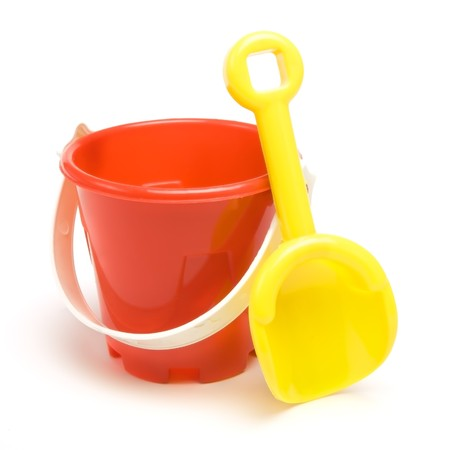 Kids red bucket and yellow spade summer holiday concept isolated against white background.