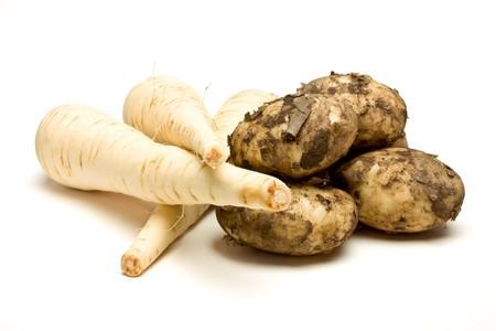 root vegetables: Verdure di radice di nuovo patate e Pastinaca sativa dal punto di vista basso isolato su sfondo bianco.