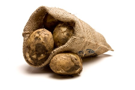 Sack of new Potatoes from low perspective isolated against white background. photo