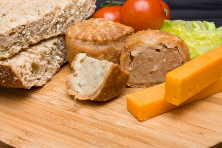 Traditional English Ploughmans Lunch of cheese, bread, tomato, lettuce and pork pie on wooden platter. photo