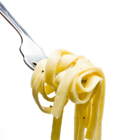pasta fork: Pasta ribbons tossed in olive oil, salt and pepper on fork isolated against white. Archivio Fotografico