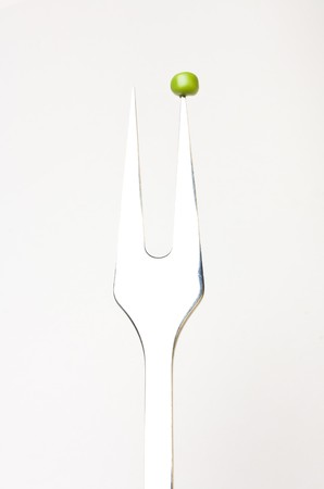 Abstract image of single pea on fork concept isolated against white. Standard-Bild