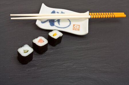 dark grey slate: Sushi and chopsticks on dark grey slate background.