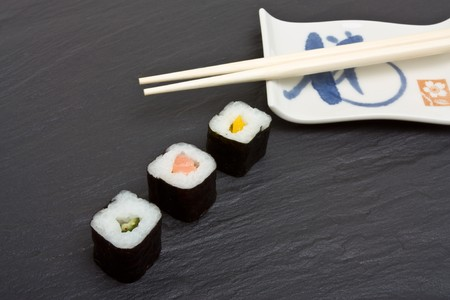 Sushi and chopsticks on dark grey slate background. photo