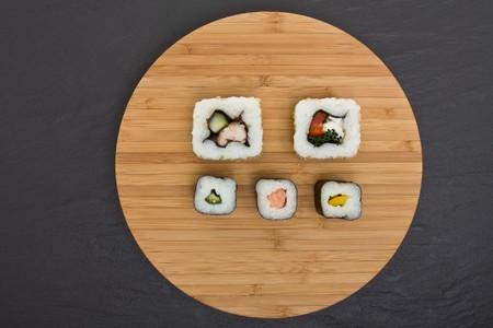dark grey slate: Sushi and bamboo board on dark grey slate background. Stock Photo