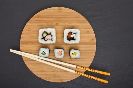 dark grey slate: Sushi and bamboo board with chopsticks on dark grey slate background.