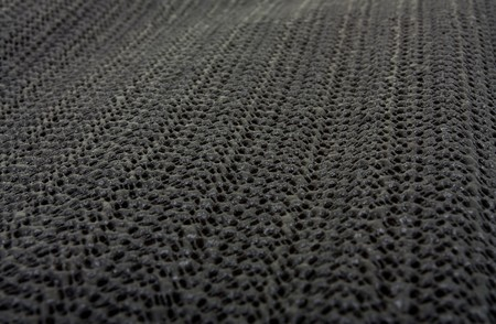 rubber: Black non slip Silicon or rubber mat background or texture with shallow focus and diminishing perspective. Stock Photo
