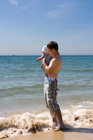 Young Father and 2-3 month old baby son at beach for first time. photo
