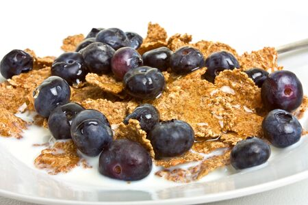 Breakfast Cereal Medley of bran flakes, blueberries, honey and milk. photo