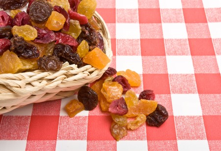 Dried Fruits of apricot, sultana, raisins and cranberries spilling onto red and white tablecloth. photo