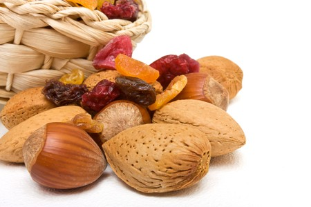 raisin: Mixed dried fruits and nuts spilling from basket on white background. Stock Photo