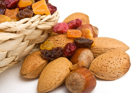 Mixed dried fruits and nuts spilling from basket on white background. photo