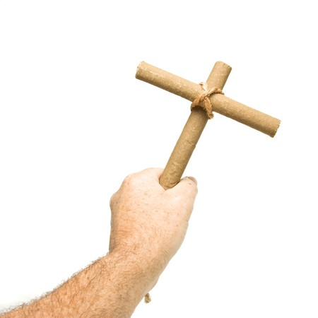 Anti Smoking concept of male hand holding crucifix made from 2 cigars tied with rope isolated on white. photo