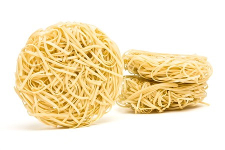 ribbon pasta: Nests of dried noodles from low perspective isolated on white.