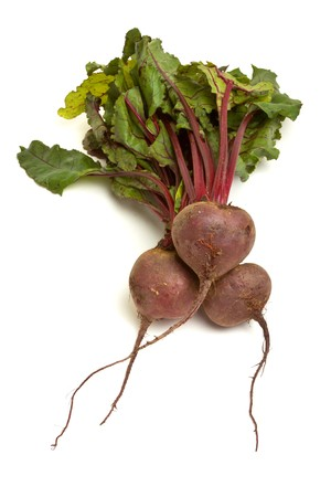 Freshly picked beetroot with their roots and tops isolated against white.