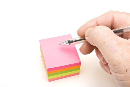 Block of vibrant multicoloured Post it Notes isolated on white with hand holding pen and copy space. Stock Photo - 7919256