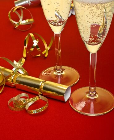 Festive celebration concept of champagne, ribbons and crackers under a golden light. photo