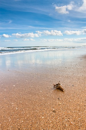 Sunny beach with blue sky, clouds and breaking waves on Northumberland coast, North East England.