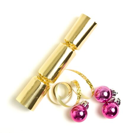 Golden Christmas Cracker with ribbon and pink baubles from overhead. photo