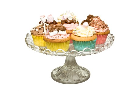 cake stand: A selection of fancy homemade cupcake on glass pedestal cake stand. Stock Photo