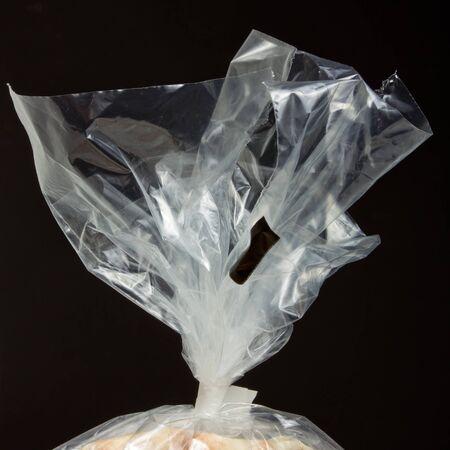 Col du sac de plastique transparent alimentaire avec cravate sur fond sombre.